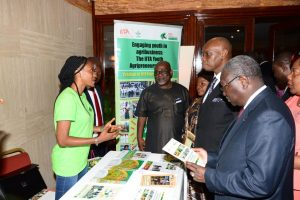 Picture of Tola, a youth Agripreneur, explaining the IYA program to the Minister of Agriculture, H.E Henri Eyebe Ayissi