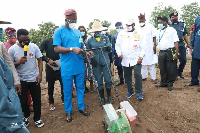 A STEP-trained student showing Governor Seyi Makinde how to use a planter.